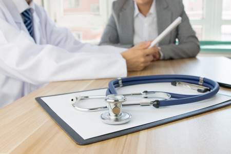 Close up of  stethoscope with Doctor and patient at the background Imagens