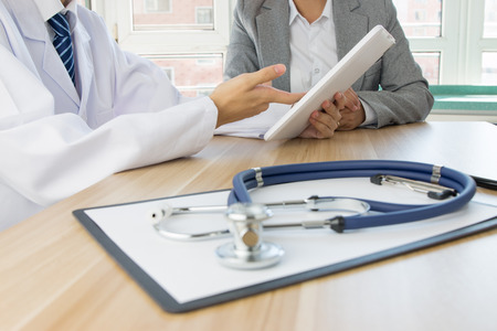 stethoscope close up with Doctor and patient behind