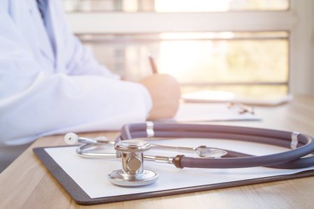 medical person: Close-up of stethoscope and folder on background of doctors at work Stock Photo