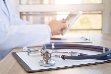 doctors tools: Close-up of stethoscope and folder on background of doctors at work Stock Photo