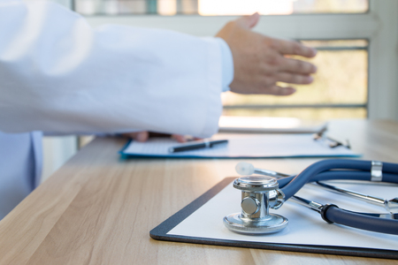 working place: Close-up of stethoscope and folder on background of doctors at work Stock Photo