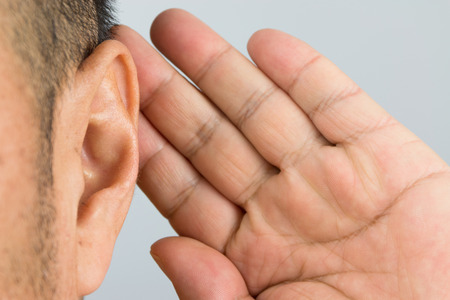 his: man holds his hand near his ear and listening Stock Photo