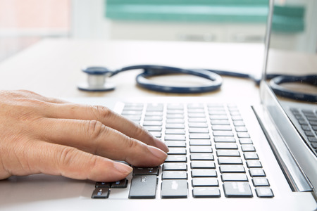 Close up of doctors hand at computer typing