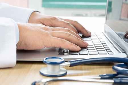 Close up of doctor's hand at computer typing