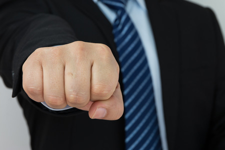 clench: Businessman fist protrudes Stock Photo