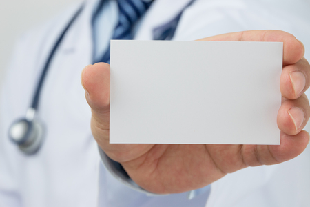 Doctors hand holding a business card Stock Photo