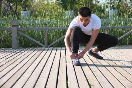 close up man runner tying shoelaces