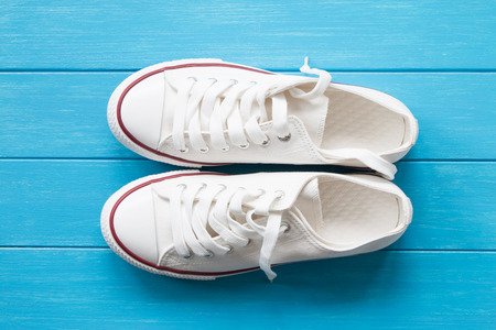 white canvas: A pair of white canvas shoes on a blue wooden Stock Photo