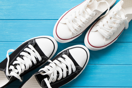 Two pairs of canvas shoes on a blue wooden
