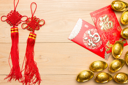 gold ingot: Chinese New Year red envelope and gold ingot in wood Stock Photo