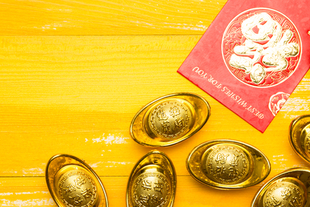 ingots: Chinese New Year red envelope and gold ingot in yellow wood