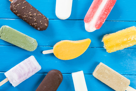 Colorful ice pops in blue wooden background