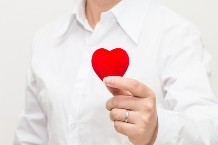 Womans hand holding a heart shape