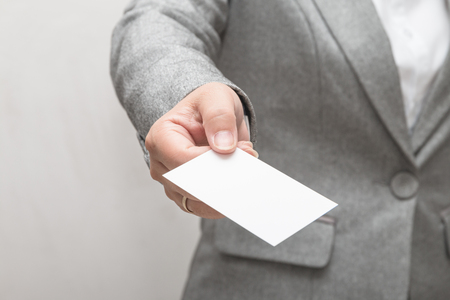 Womans hand holding a business card