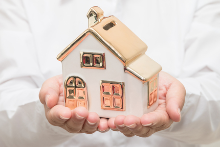Womans hands holding house model Stock Photo