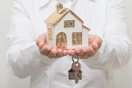 Womans hands holding house model with key Stock Photo