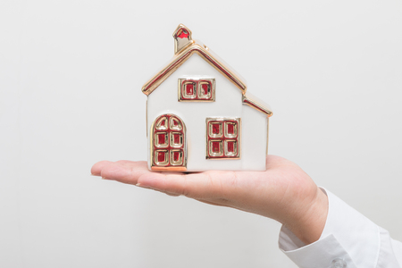 Womans hand holding house model Stock Photo