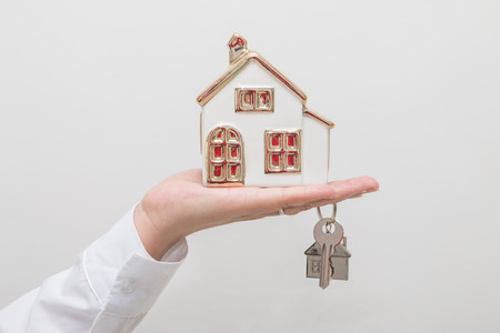 Womans hand holding house model and key
