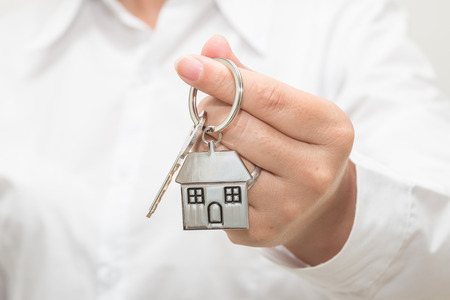 Womans hand holding a house key Stock Photo