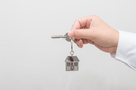 Woman's hand holding a house key Stock Photo - 113639440