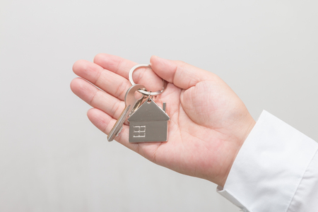 Woman's hand holding a house key Stock Photo - 113639444