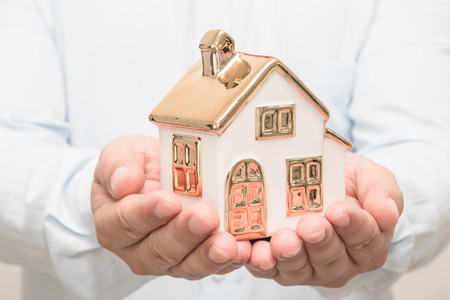 Man's hands holding house model Stock Photo - 113639623