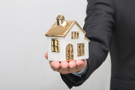 Man's hand holding house model Stock Photo - 113639628