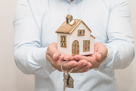 Man's hands holding house model and key Stock Photo - 113639631