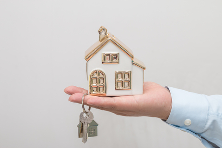 Man's hand holding house model and key Stock Photo - 113639656