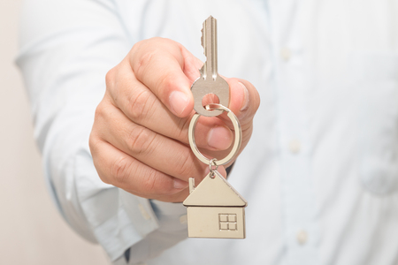 Man's hand holding a house key Stock Photo - 113639680