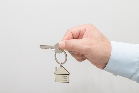 Man's hand holding a house key Stock Photo - 113639682