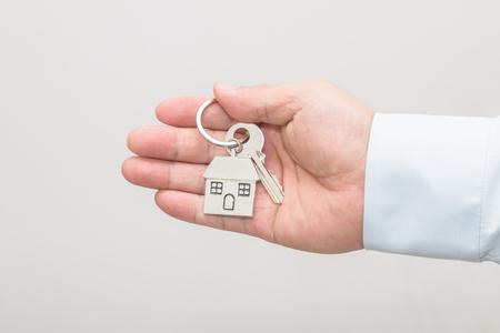 Man's hand holding a house key Stock Photo - 113639689