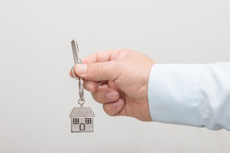 Man's hand holding a house key Stock Photo - 113639703