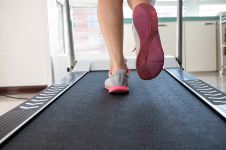 Woman doing fitness on a treadmill Stock Photo - 115866281
