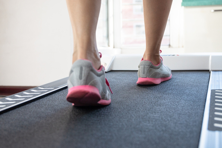 Woman doing fitness on a treadmill Stock Photo - 115866290