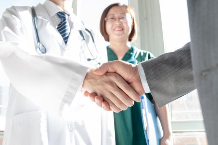 Doctor and business people shaking hands Stock Photo - 117097879
