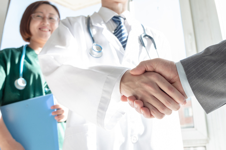 Doctor and business people shaking hands Stock Photo - 117097880