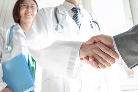 Doctor and business people shaking hands Stock Photo