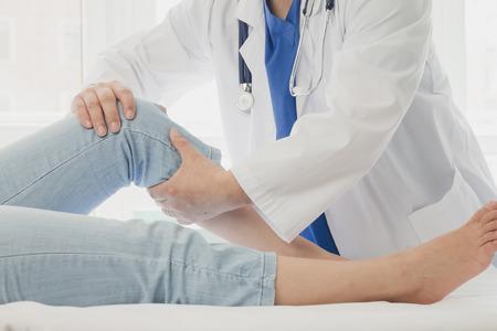 Doctor dando a un paciente un tratamiento de piernas