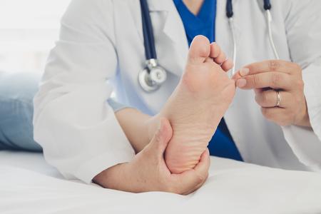 Dottore che fa un trattamento ai piedi del paziente