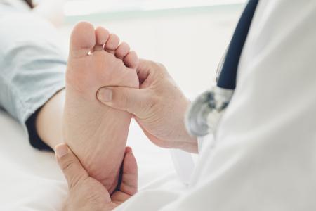 Doctor dando un tratamiento de pie de paciente