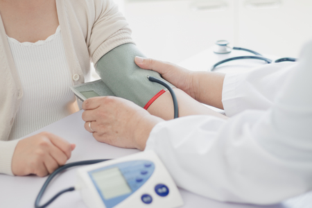 The doctor measures blood pressure to the patient