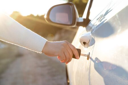 Mujer toma la llave para conducir la puerta del auto Foto de archivo