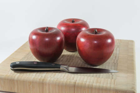 paring knife: Bamboo cutting board, with wooden apples and a paring knife Stock Photo