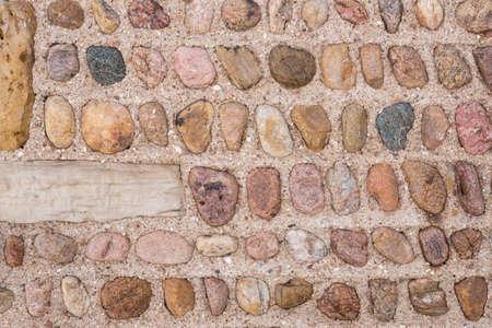 man made object: Stone Wall.  Interesting symmetrical masonry using round stones offset by square masonry blocks
