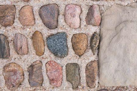 Stone Wall.  Interesting symmetrical masonry using round stones offset by square masonry blocks