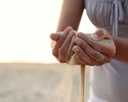 reloj de arena: Tiempo a medida que la arena se desliza entre los dedos.