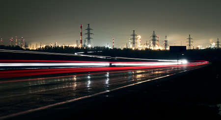 Car lights on a highway at night on the background of the industrial landscape.