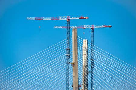 shrouds: White shrouds, pylons and bridge cranes on the blue background Stock Photo