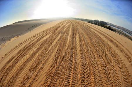 car tracks on the yellow sand in desert in Vietnam photo